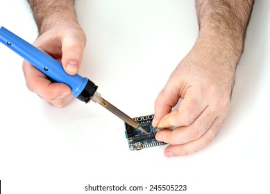 Male hand holding a soldering iron and repair electronic chip