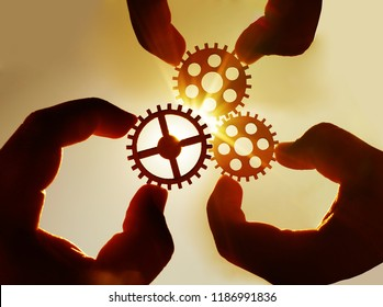 Male hand holding three wooden cog gear wheel on blue sky background. sunshine and yellow sky .