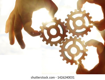 Male hand holding three wooden cog gear wheel on sunny sky background. sunshine and yellow and yellow sky . sun rays.one part of whole. symbol of association and connection. business strategy