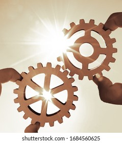 Male hand holding three wooden cog gear wheel on sunny sky background. sunshine and blue sky . sun rays.one part of whole. symbol of association and connection. business strategy