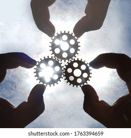 Male hand holding three wooden cog gear wheel on sunny sky background. sunshine and blue sky . sun rays.one part of whole. symbol of association and connection. business strategy.