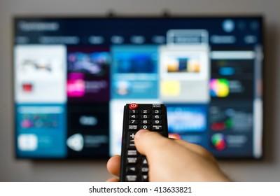 Main masculine tenant la télécommande de la télévision.