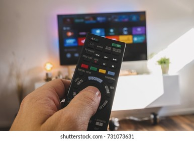 Male hand holding TV remote control, Point of view shot