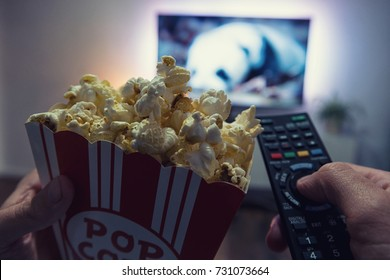 Male hand holding TV remote control and popcorn box, Point of view shot