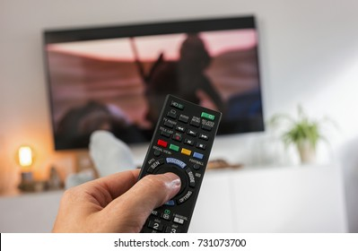 Male hand holding TV remote control and Watch tv