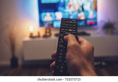 Male hand holding TV remote control. Point of view shot