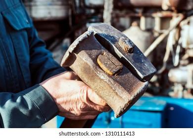 Male hand holding two big hammer, sledgehammer. Repairing tractor engine. Mechanic repairing tractor.