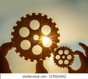 Male hand holding two iron cog gear wheel on sunny sky background. sunshine and yellow and blue sky . sun rays.