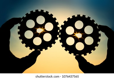 Male hand holding two wooden cog gear wheel  on sunny sky background. sunshine and yellow and blue sky . sun rays.