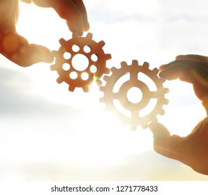 Male hand holding two wooden cog gear wheel on sunny sky background. sunshine and yellow and yellow sky . sun rays.one part of whole. symbol of association and connection. business strategy