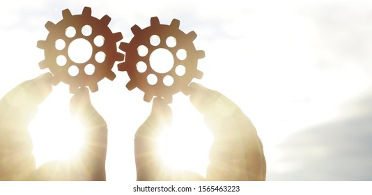 Male hand holding two wooden cog gear wheel on sunny sky background. sunshine and yellow and yellow sky . sun rays.one part of whole. symbol of association and connection. business strategy.