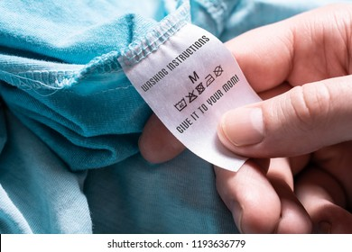 Male Hand Holding A Washing Instruction With A Give It To Your Mom Advice - Doing Laundry For Beginners Concept