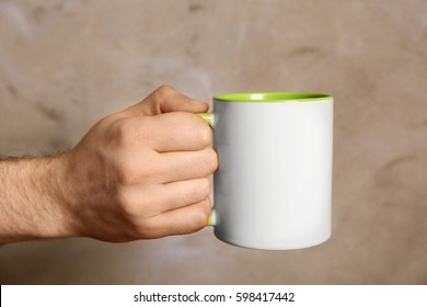 Male hand holding white cup on blurred background