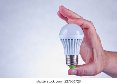 Male hand holding a white led light bulb