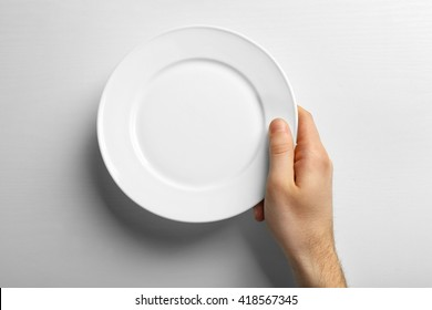 Male hand holding white plate, isolated on white
