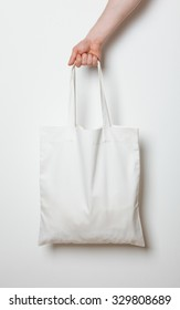 Male hand holding white textile bag, neutral background