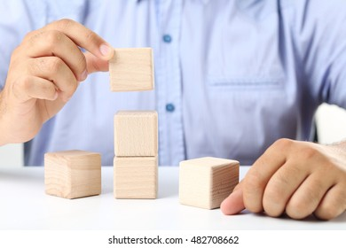 Male hand holding the wooden cube
