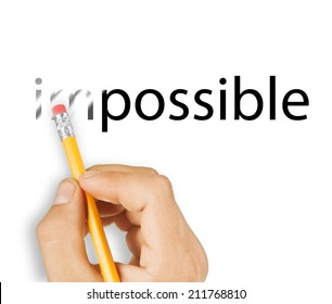 "Male hand holding wooden pencil and erase letters ""IM"" from word ""IMPOSSIBLE"
