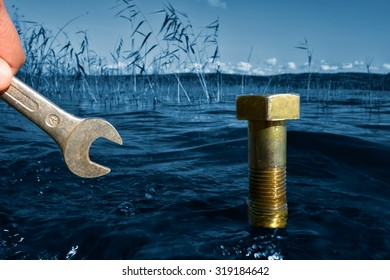 Male hand holding a wrench in front of a bolt coming out of the blue selective color lake water on a sunny Autumn afternoon in Finland with ecology, environmental protection and green concept idea.