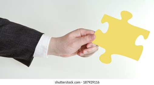male hand holding yellow puzzle piece on grey background