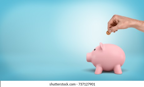 A male hand holds a 50 cent coin above a slit on piggy bank's back on blue background. Saving up money. Careful investment. Risk free finances.
