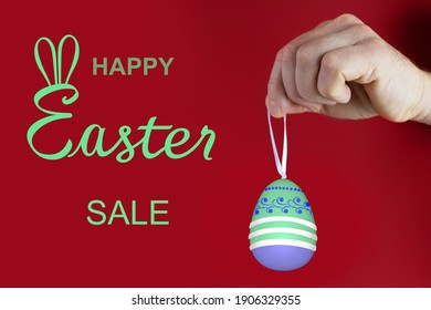 male hand holds a colored Easter egg with a drawn pattern, red background, concept of Christian traditions, holidays, Spring Festival
