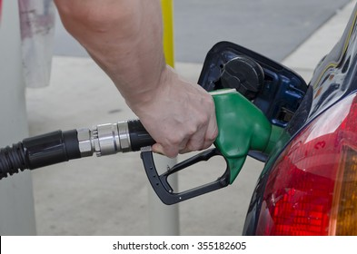 Male hand holds a fuel pump nozzle filling up car with petrol at a petrol station. Car tail light and petrol filling door on image. Car is dark blue and petrol nozzle is green. Horizontal image.