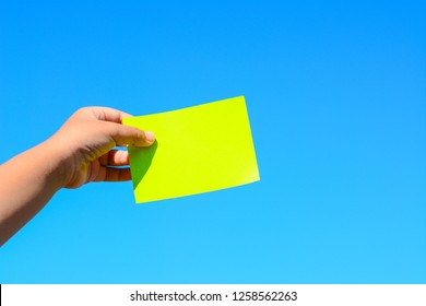 A male hand holds a green paper card with the blue sea as a background.