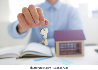 Male hand holds the key to the lock in the hand against the backdrop of the toy house sale purchase lease concept real estate services on the market