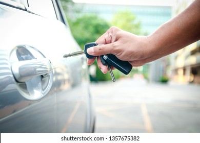 The male hand holds the key to unlock the door to open the car.