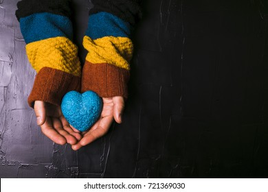 Male hand holds out a blue heart on black background
