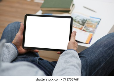 Male hand holds tablet pad in home setting while sitting on the couch engaged an internet surfing using application to press a finger on the display leisure listering music concept closeup.