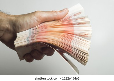 Male hand holds a thick stack of cash money. Million Russian rubles. The concept of rich, wealth, profits, business and finance. Five thousandth bills banknotes. A lots wads of money