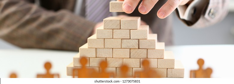 Male hand holds wood block of stair finish next step rare progress personnel talent authority hot pyramid background on ladder different insurance concept closeup