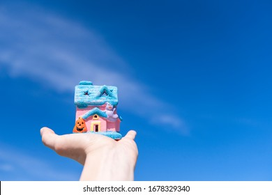 Male hand holds wooden house on blue sunny sky background.  Image of buying a house.