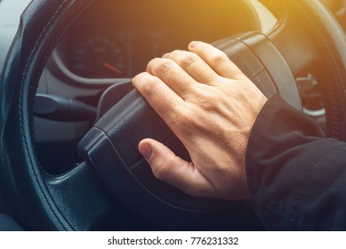Male hand honking the car horn, man driving vehicle and beeping