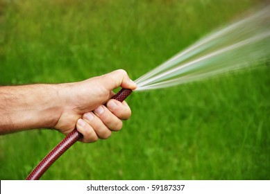 male hand with a hose watering grass