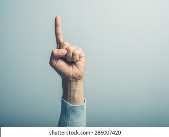 A male hand with the index finger pointing up