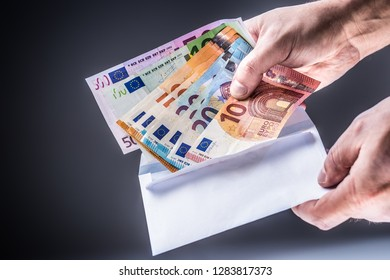 Male hand inserted into the envelope euro banknotes - bribe and corruption concept.