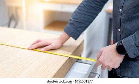 Male hand interior designer using tape measure for measuring size of wooden countertop in modern kitchen showroom in furniture store. Shopping material design for home improvement.