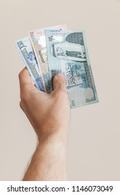 Male hand with Jordanian dinars banknotes over gray background, vertical photo