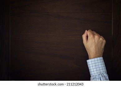 Male hand is knocking on wooden door, conceptual image. Visitor or guest is at the door.