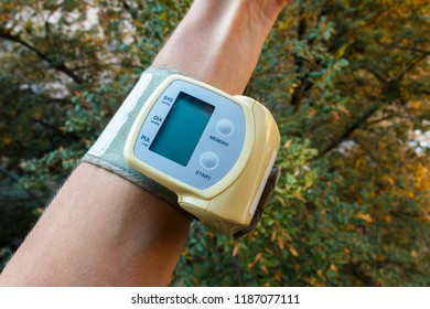 Male hand with little electric tonometer measuring blood pressure. Medicine, age, healthcare and people concept with tonometer on the green background. The tonometer is on hand. Arterial pressure