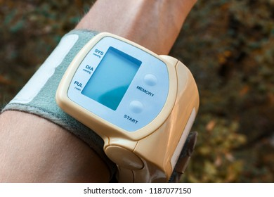 Male hand with little electric tonometer measuring blood pressure. Medicine, age, healthcare and people concept with tonometer on the green background
