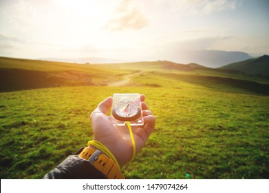 Male hand with a magnetic compass ea against the backdrop of a beautiful landscape at sunset. The concept of navigating the search for your own path and orientation to the cardinal points