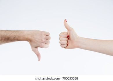 A male hand making thumb down and a female hand making thumb up