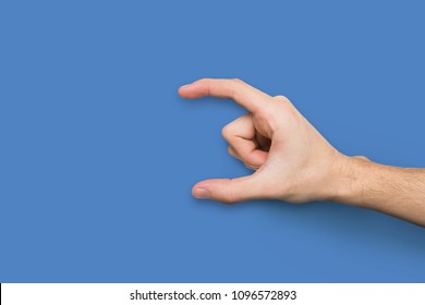 Male hand measuring invisible items, man's palm making gesture while showing small amount of something or holding credit card on blue background, copy space, void