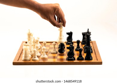 Male hand moving the white chess queen during the game of chess. Isolated on white.