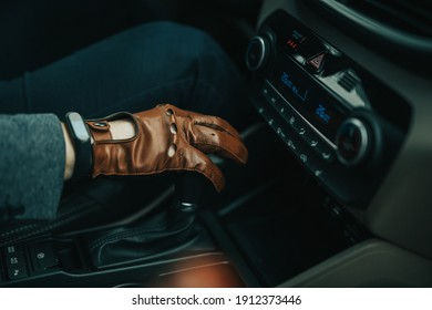 Male hand on gearstick of a manual car with brown leather driver gloves on and black smartwatch on right hand