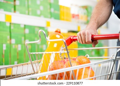 Male hand on shopping cart at supermarket close-up.